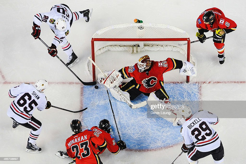 <a gi-track='captionPersonalityLinkClicked' href=/galleries/search?phrase=Reto+Berra&family=editorial&specificpeople=570422 ng-click='$event.stopPropagation()'>Reto Berra</a> #29 of the Calgary Flames stops the wrap-around attempt by <a gi-track='captionPersonalityLinkClicked' href=/galleries/search?phrase=Brandon+Saad&family=editorial&specificpeople=7128385 ng-click='$event.stopPropagation()'>Brandon Saad</a> #20 of the Chicago Blackhawks during an NHL game at Scotiabank Saddledome on January 28, 2014 in Calgary, Alberta, Canada. The Flames defeated the Blackhawks 5-4 in overtime.