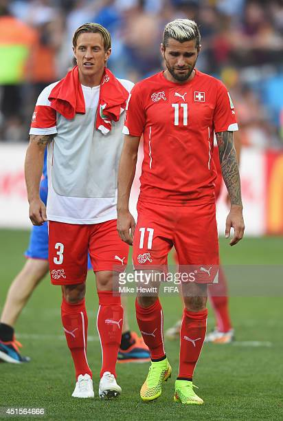 Reto Ziegler of Switzerland and Valon Behrami of Switzerland show their dejection as they walk off the pitch after the 01 defeat in the 2014 FIFA...