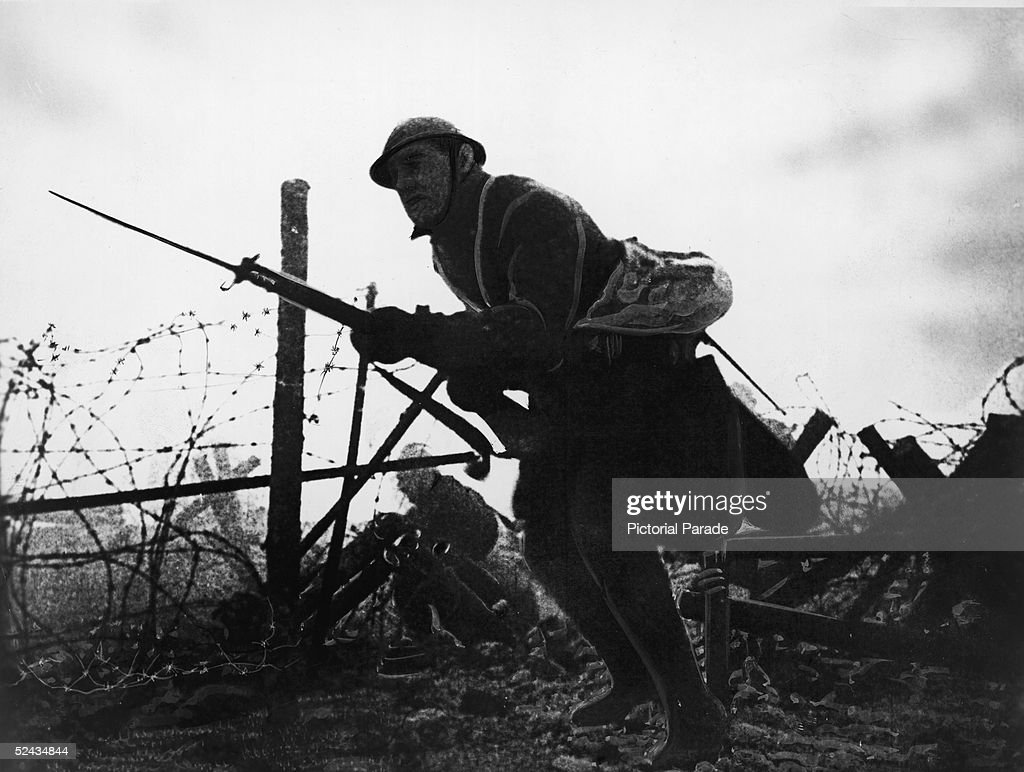 Retouched photograph of an Allied soldier as he stands with fixed bayonet across No Man's Land amid barbed wire obstacles during a battle on the Western Front, France, World War One.