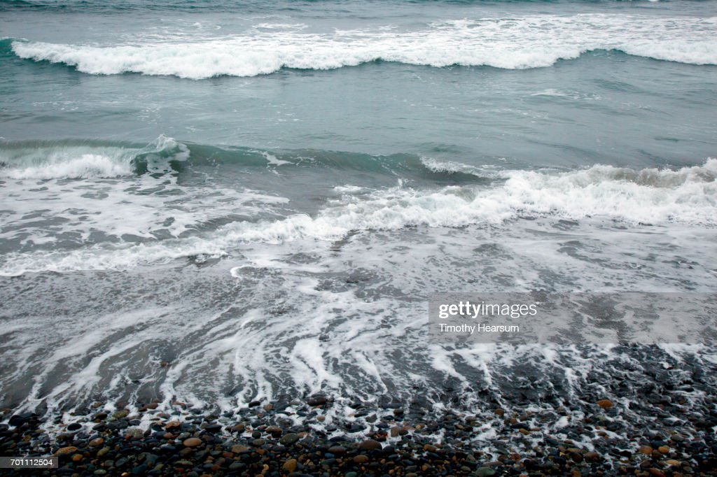Retreating waves on a rocky beach with incoming waves beyond : Stock Photo