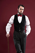 Retro 1900 victorian fashion man with beard wearing black gilet and red bow tie. Holding a walking stick. Studio shot against red wall.