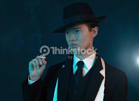retro 1940 asian gangster fashion man holding cigarette stock photo