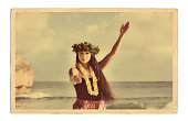 A retro old vintage style photo postcard look of a beautiful Hawaiian Hula dancer dancing on the beach of the tropical Hawaiian islands. Photographed in horizontal format with copy space in Kauai, Haw