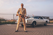 Retro 1970s gangster holding gun standing in front of vintage car.