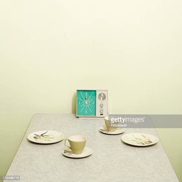 Retro 50's table setting with dishes coffee cups and vintage clock radio