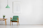 Retro concept mint pastel armchair, wooden table and framed poster in a bright minimalist interior with copy space