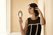 Retro beauty adjusting her hair in a silver mirror