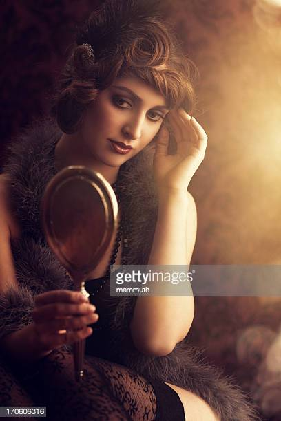 retro beauty lookin at herself in a silver hand mirror