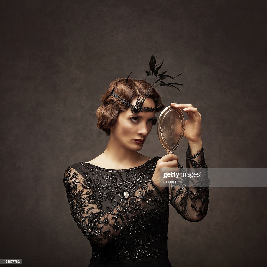 retro beauty looking at herself in a silver hand mirror