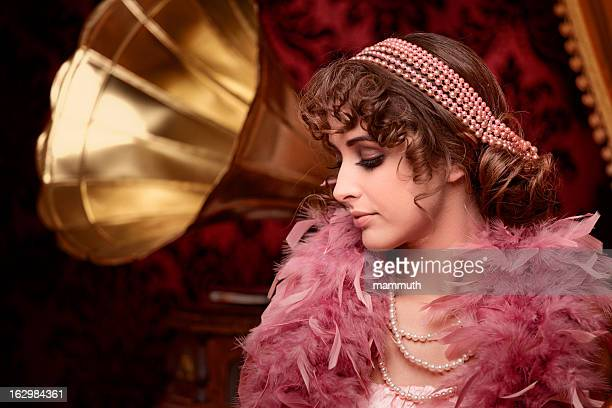 retro beuty with feather boa listening music in boudoir