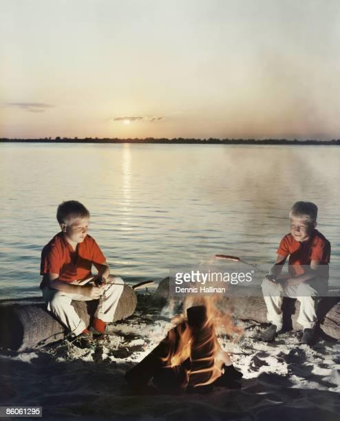 Retro boys roasting hot dogs over fire