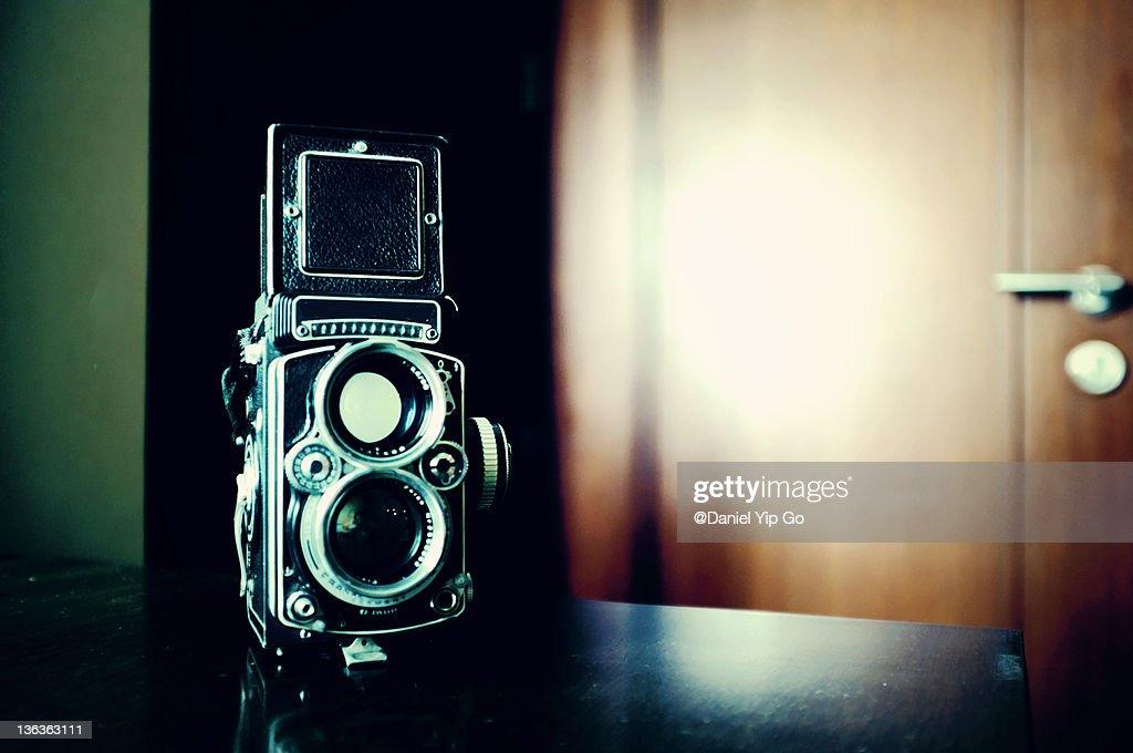 Retro camera near by wooden door : Stock Photo