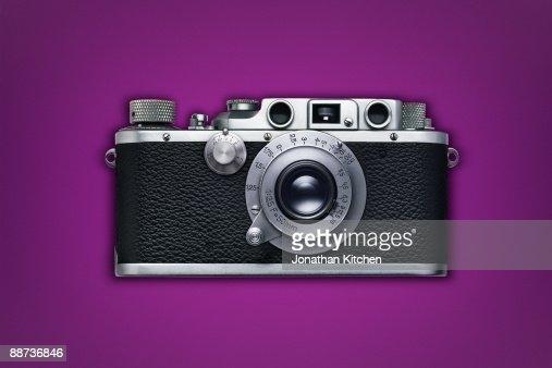 Retro camera on coloured background