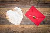 Old style Valentine's Day cad and idea, love letter, love symbol, painted wooden hart isolated, wax sealed envelope on antique oak panels - top view