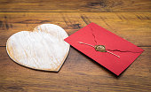 Old style Valentine's Day cad and idea, love letter, love symbol, painted wooden hart isolated, wax sealed envelope on antique oak panels - front view