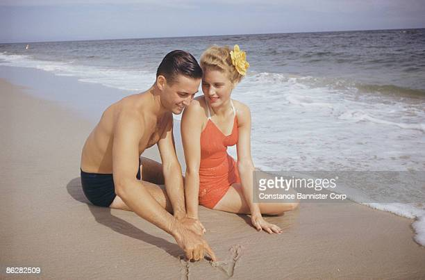 Retro couple at the beach drawing names in the sand