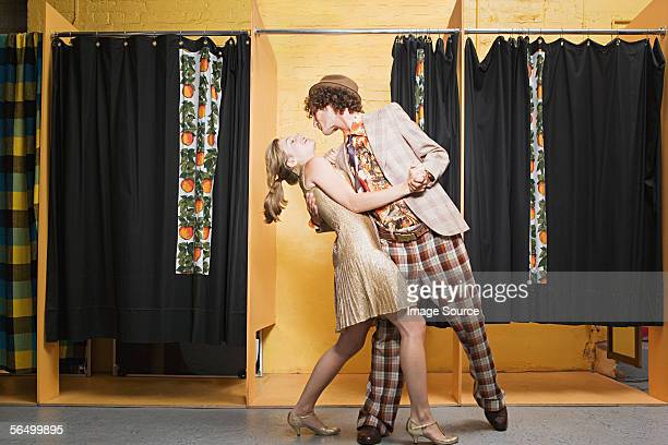 Retro couple dancing in clothes store