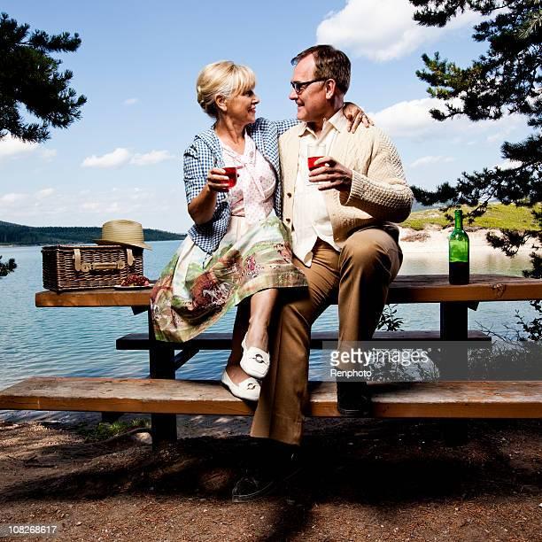 Retro paar sitzend mit Picknick-Tisch, trinken Wein