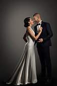 Retro Couple, Well Dressed Woman in Long White Dress and Elegant Man in Black Suit, Studio Full Length Portrait over black background