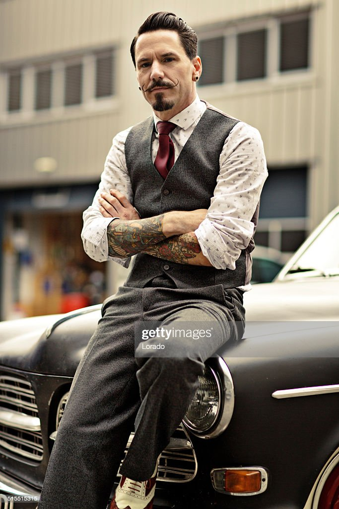 Retro Dressed Man With Moustaches Sitting On His Car Stock Photo