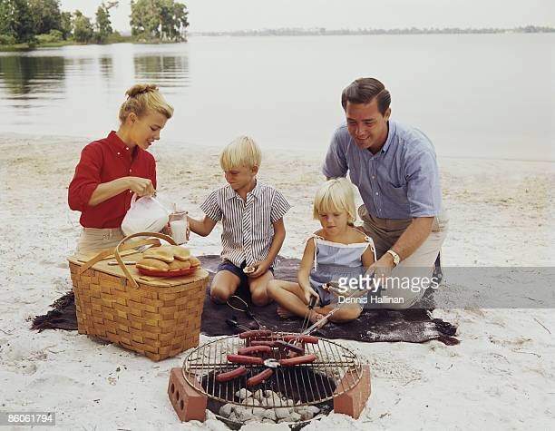 Retro family enjoying barbeque on the beach
