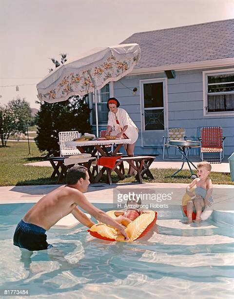Retro Family In Backyard, Showing An In-Ground Swimming Pool, Father, Mother, Son, Daughter, Man, Woman, Boy, Girl.