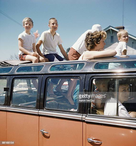 Retro family sitting on roof of van bus enjoying day trip