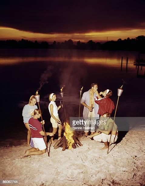 Retro friends enjoying a bonfire at the beach