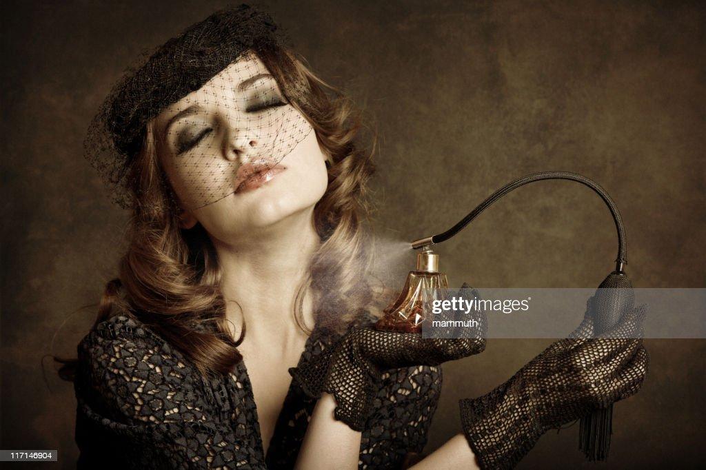 Retro girl applying perfume : Stock Photo