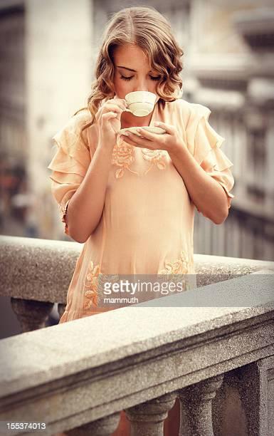 Fille rétro, boire du café sur le balcon