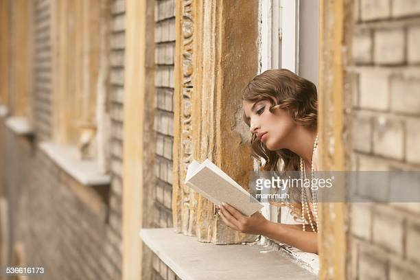 Retrò la ragazza leggendo un libro nella finestra