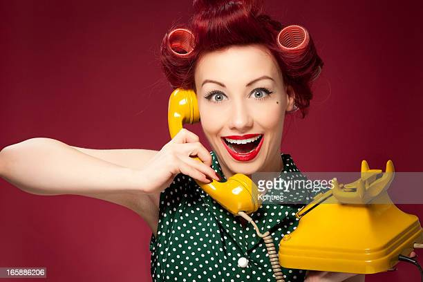 Retro housewife holding vintage yellow phone