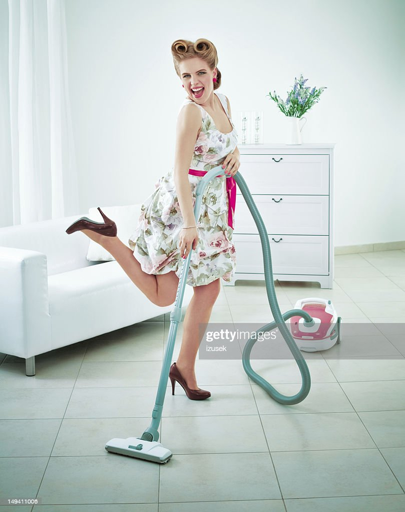 Retro housewife vacuuming a floor : Stock Photo