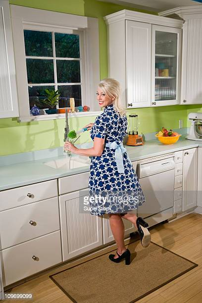 Retro housewife washing dishes at kitchen sink