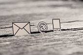 Retro image of business communications concept with icons for email, a web address and telephone on rustic wooden table.