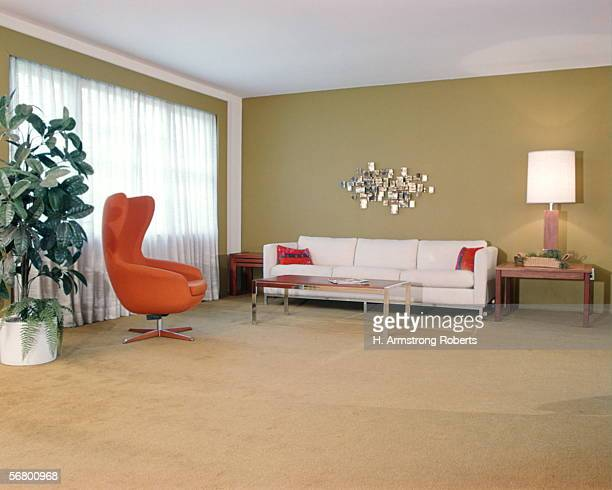 Retro living room interior with orange chair and white sofa