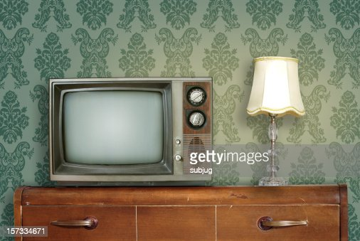 retro living room with a tv and a lamp atop a wooden desk stock