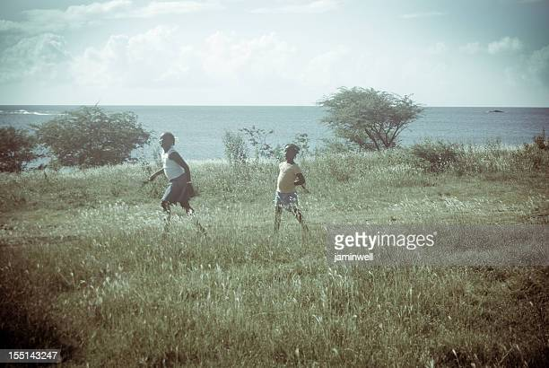 retro look; girls running in grassy field with sea landscape