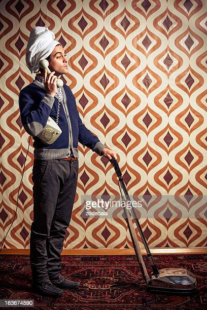 Retro Man Using Vacuum Cleaner and Talking to the Phone