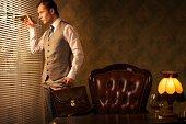 Retro man with a briefcase looking through jalousie.