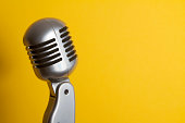 Retro Microphone in front of a yellow backround.See also: