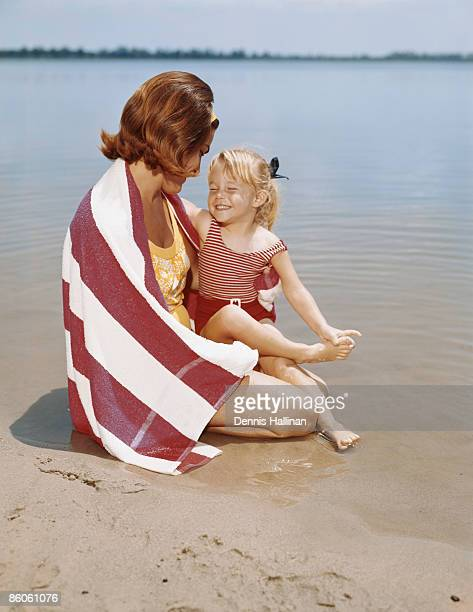 Retro mother and daughter lying down on lakeshore