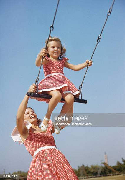 Retro mother and daughter playing in swing