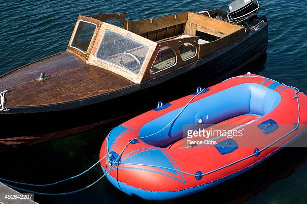 A retro motorboat moored next to a new inflatable boat