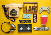 Retro objects on a yellow background. Rotary telephone, audio cassette, video cassette, gamepad, 3d glasses, tv remote, headphones, push-button phone. Analog media technology of the past. Flat lay.