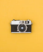 front view of old fashioned eighties camera on yellow background.