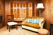 """Photo of a reading room furnished with out-of-date furniture, carpet and fixtures."""