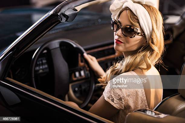 Retro style woman in an old timer car.