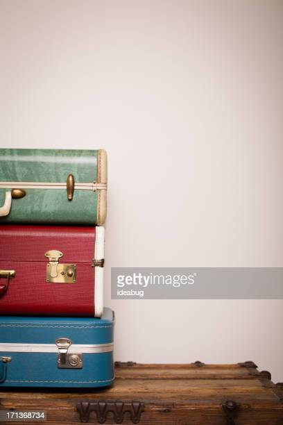 Retro Suitcases Stacked on Wood Trunk, With Copy Space