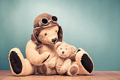 Retro Teddy Bear toy in leather pilot's hat and vintage goggles playing with baby front mint green wall background. Old style filtered photo